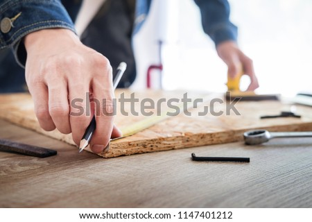 Carpenter working carefully looking at the plans work in carpentry. He is successful entrepreneur at his workplace. hammering a nail Supports On Building Site work with cutter