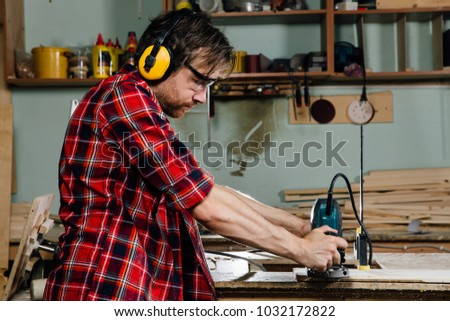 Carpenter working of manual hand milling machine in the carpentry workshop. joiner, woodworker red checkered shirt, jeans. Ear-eye protection.