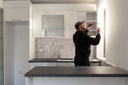 Carpenter working on new kitchen. Handyman fixing a door in a kitchen