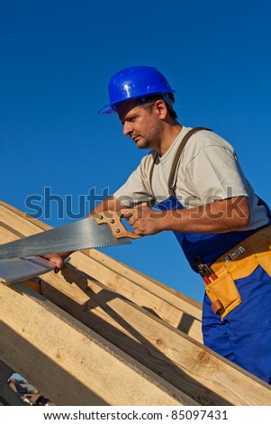 Carpenter working on the roof with a saw