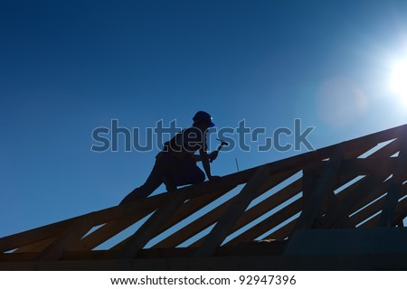 Carpenter working on top of the roof wooden structure - strong back light silhouette