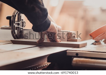 Carpenter working on woodworking machines in carpentry shop. A man works in a carpentry shop. Saws furniture details with a circular saw. another view close