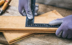 Carpenter working with a square metal angle