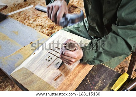 Carpenter working with chisel - Shutterstock ID 168115130
