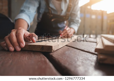 Carpenter working with equipment on wooden table in carpentry shop. woman works in a carpentry shop. #1296777334
