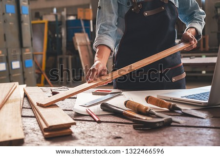 Carpenter working with equipment on wooden table in carpentry shop. woman works in a carpentry shop. #1322466596
