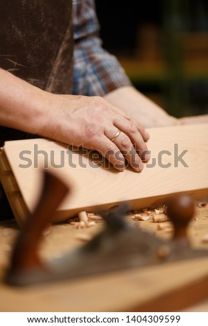 Carpenter working with wood parts and planer on the workbench #1404309599