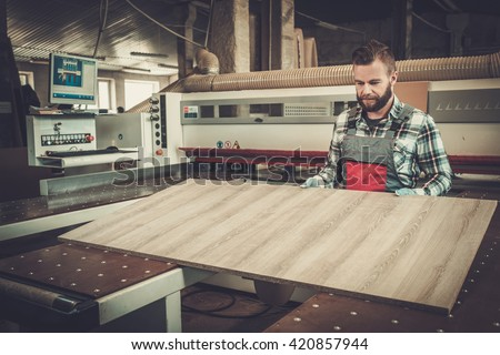 Carpenter works on wood plank in carpentry workshop.