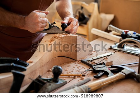 Carpenter works with a planer in a workshop for the production of vintage furniture. He makes cabriole leg for a table in the style of Louis and Queen Anne/Joiner Makes Cabriole Leg for Vintage Table Photo stock ©