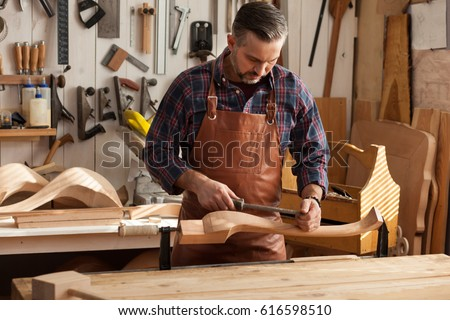 Carpenter works with a planer in a workshop for the production of vintage furniture. He makes cabriole leg for a table in the style of Queen Anne/Joiner Makes Cabriole Leg for Vintage Table Photo stock ©