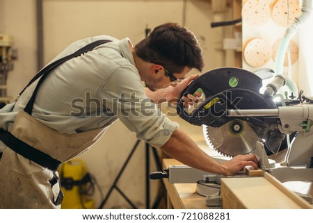 carpenters cutting wooden plank with a circular saw