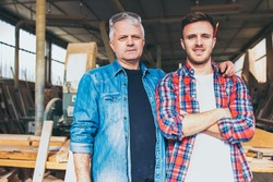 Carpenters standing proud in front of a workshop, family business