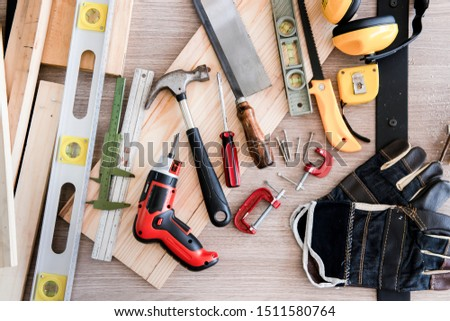 carpentry headphones.saw,small piece of wood,electric screwdriver,spirit level,plank,wood,measurement,level tools,tape measure,plank wood,sawing the wood,C-clamp,G-clamp,woodwork,instruments on table