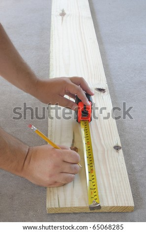 Carpentry, mans hand using tape measure to measure wood plank and marking it with pencil