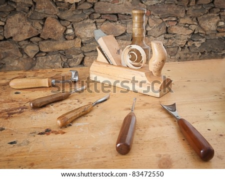 Carpentry tools spread on wooden table with stone wall in the background.