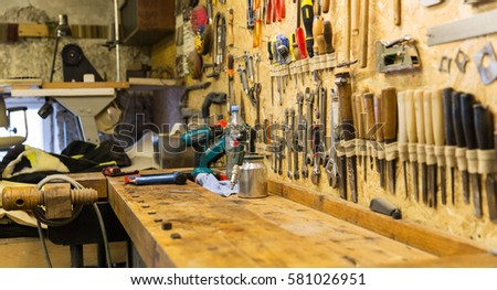 carpentry, woodwork and equipment concept - work tools and workbench at workshop