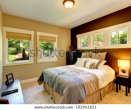 Carpet bedroom with contrast color wall. Beautiful bedding.