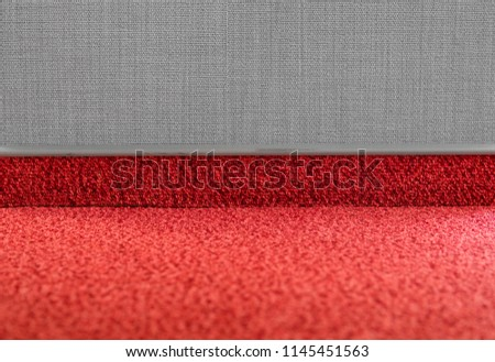 Carpet floor with a carpet baseboard on a grey wall.