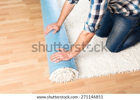 Carpet. Repair, building and home concept - close up of male hands unrolling carpet