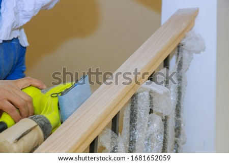 Carpeted in refinishing in the stairwell of railing in a sandpaper sanding stock photo