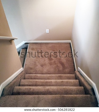 Carpeted interior stairway with landing with light shining up the staircase from a window on a lower floor. stock photo