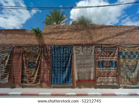 Carpets for sale hanging on a wall along the road near Fes in Morocco