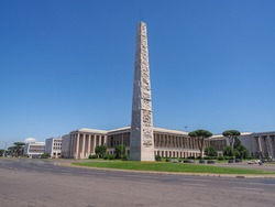 Carrara marble Obelisk of Marconi or EUR in the blue sky background. Truncated pyramid shape Obelisco di Marconi with relief sculptures representing the history of Italian emigrants around the world.