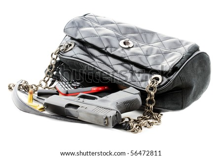 Carried concealed. Handgun and accessories falling from a woman's purse. Isolated on white with light shadow.