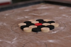 Carrom men and one striker, arranged at the start of a game