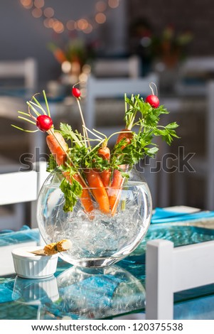 Carrot and berries decorations in a glass vase.