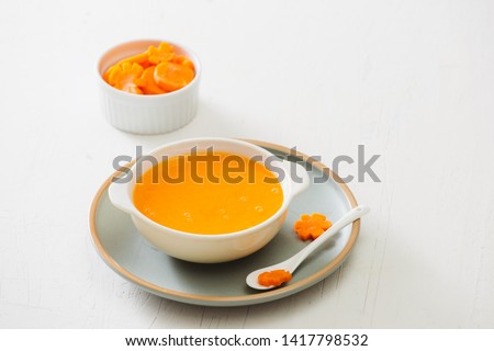 Carrot baby puree in bowl isolated on light background #1417798532