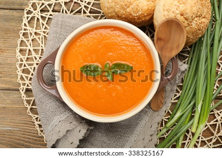 Carrot cream-soup with buns on table close up #338325167