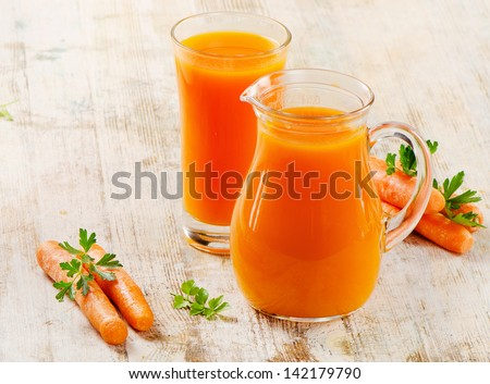 Carrot juice  and carrots on a wooden table. Selective focus