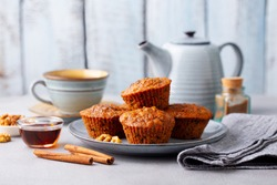 Carrot muffins, cakes with cup of tea. Grey background.