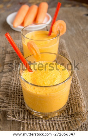 Carrot smoothie on wooden background, vertical close up