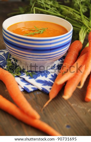 Carrot soup in a blue bowl with fresh carrot on side