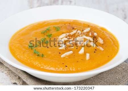 carrot soup with almonds and watercress on white wooden table, close-up, horizontal - stock photo