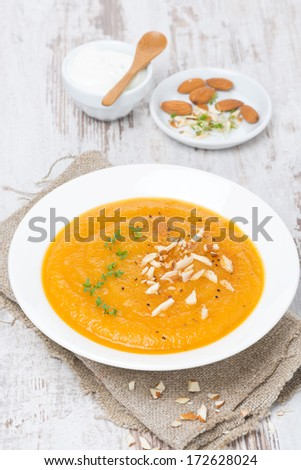 carrot soup with almonds and watercress on white wooden table, vertical - stock photo