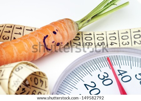Carrot with a face on a body scale with tape measure / diet