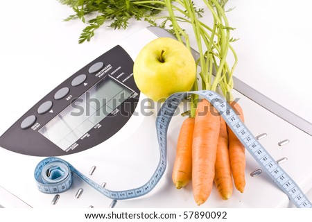 Carrots and apple surrounded by a measuring tape on a white bathroom scale. Blank display.