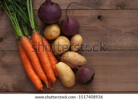 Carrots, beets and potatoes on a wooden background. Harvest season #1517408936