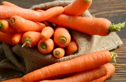 Carrots in sack bag on wooden floor. Carrots provide a number of nutrients other than beta-carotene. They are rich in fiber.