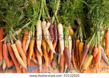 Carrots of several colors arranged on table at farmers market