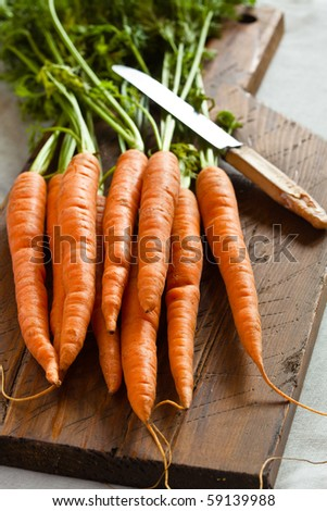 Carrots unwashed on a chopping board