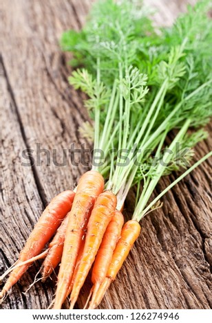 Carrots with leaves on a old wooden table.