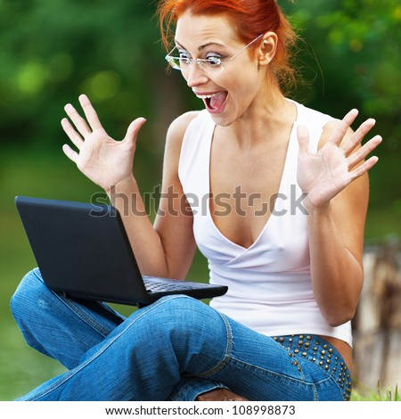 Carroty beautiful woman with joy and delight in watching laptop screen, on green park summer.