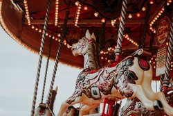 Carrousel horses on merry-go-round with bright lights at sea side town, Brighton