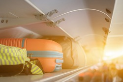 Carry-on luggage on the top shelf over head on airplane, passenger put bag cabin compartment air craft business class,vintage color,copy space