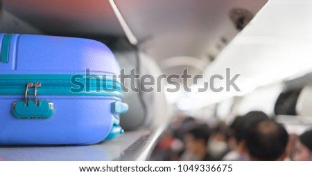 Carry-on luggage on the top shelf  over head on airplane, passenger put bag cabin compartment air craft ,vintage color,copy space