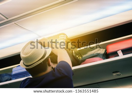 Carry-on luggage on the top shelf over head on airplane, passenger put bag cabin compartment air craft business class,vintage color